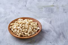 Peanuts in wooden plate over white textured background, top view, close-up. Shelled peanuts in wooden plate over white textured background, top view, close-up stock image