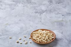 Peanuts in wooden plate over white textured background, top view, close-up. Shelled peanuts in wooden plate over white textured background, top view, close-up royalty free stock photo
