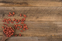 Peanuts in wooden spoon on old wooden background. Royalty Free Stock Photography