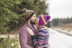 年轻peaople在冬天森林里亲吻 免版税库存照片