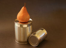 Pear and aluminum cans. Pear with two aluminum cans on brown background Royalty Free Stock Photo