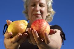 Pear or apple?. Woman with pear and apple Stock Photography