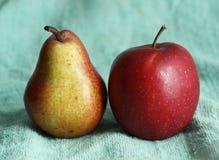 Pear and apple on blue cloth as an art composition Stock Photos