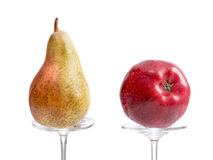 Pear and apple presented on glass stem Stock Photos