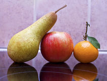 Pear, apple and tangerine still life Stock Image