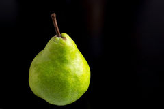 Pear in black. Green Pear in black table Royalty Free Stock Photography