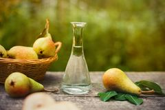 Pear with bottle of fruit brandy. Fresh pear with bottle of fruit brandy on the table royalty free stock images