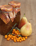 Pear-buckthorn jam. Sea buckthorn-pear jam in banks and pear and sea buckthorn berries nearby Stock Photo