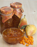 Pear-buckthorn jam. Sea buckthorn-pear jam in banks and pear and sea buckthorn berries nearby Stock Images