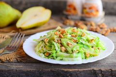 Pear and cabbage salad. Homemade salad with pear, cabbage and walnuts on a plate. Rustic wooden background. Quick healthy food Stock Image