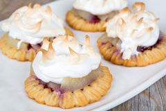 Pear cakes stuffed with jam and covered with white meringue Royalty Free Stock Photos