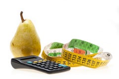 Pear, calculator and tape Royalty Free Stock Images