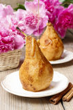 Pear with caramel, beautiful pink peonies in the background Royalty Free Stock Image