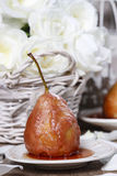 Pear with caramel sauce on grey table Royalty Free Stock Images