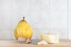 Pear and cheese, with knife, space for text. A composition with a pear and some parmigiano cheese on a wooden chopping board, inside a kitchen, space for text Royalty Free Stock Photos
