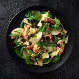 Pear, chicken salad with cheddar cheese, cranberry and walnuts. healthy food. black stone background.  stock image