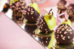 Pear in chocolate, sweet candy bar set, wedding ceremony. Pear in chocolate, stylish sweet candy bar set, wedding ceremony, confectionery stock image