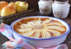 Pear clafoutis and yellow pears in wicker basket Stock Images