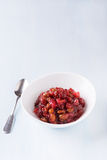 Pear cranberry relish for Christmas. In a white bowl over light blue background with copy space Stock Photo