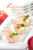 Pear and creamcheese canapes. Three mini fillo shells filled with cream cheese, pears, olives and parsley on holiday table with flute of champagne stock photography