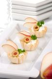 Pear and creamcheese canapes. Three mini fillo shells filled with cream cheese, pears, olives and parsley on holiday table royalty free stock photos