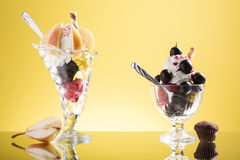 Pear cup and red grapes sundaes on yellow  backgound Royalty Free Stock Images