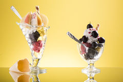 Pear cup and red grapes sundaes on yellow  backgound Royalty Free Stock Photos
