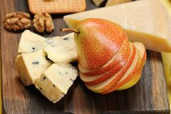 Pear cut into slices, cheese and walnuts on a wooden board Stock Image