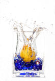 Pear Drop. Water splash picture of a pear dropping into a jug of water containing small blue glass pebbles Royalty Free Stock Image