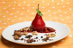 Pear flavored with red wine with Brachetto syrup and crunch nuts Royalty Free Stock Image