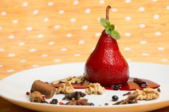 Pear flavored with red wine with Brachetto syrup and crunch nuts Royalty Free Stock Photography