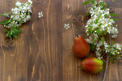 Pear and flowering branch on a wooden board. Royalty Free Stock Images