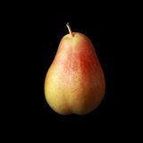 Pear isolated on black background. Closeup of yellow-red pear isolated on black background stock photo