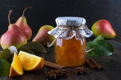 Pear jam and fresh pears cinnamon sticks, anise stars and green  leaves on the table. Royalty Free Stock Photo