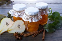 Pear jam and fresh pears cinnamon sticks, anise stars and green  leaves on the table. Stock Photo