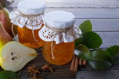 Pear jam and fresh pears cinnamon sticks, anise stars and green  leaves on the table. Royalty Free Stock Images