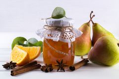 Pear jam and fresh pears cinnamon sticks, anise stars and green  leaves on the table. Stock Photos