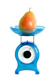 Pear on kitchen scale Royalty Free Stock Photo