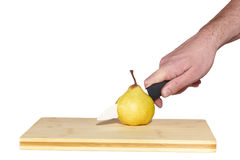 Pear with knife on chopping board Stock Image