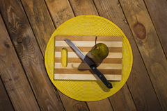 Pear and a knife lying on a cutting board. Stock Image