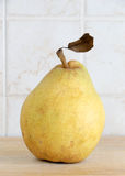 A pear with a leaf on a chopping board Royalty Free Stock Photography
