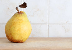 A pear with leaf inside a kitchen Royalty Free Stock Photo