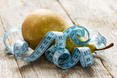 Pear and measuring tape on the  floor Stock Image