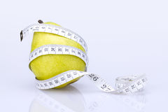 Pear and measuring tape Royalty Free Stock Photos