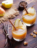Pear mulled cider with vanilla and cinnamon sticks on a wooden background Stock Photos