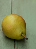 Pear. One yellow pear on old painted wooden table Royalty Free Stock Photo