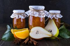 Pear and orange jam in glass jars with ripe pears, cinnamon sticks, anise stars and green leaves on the table.