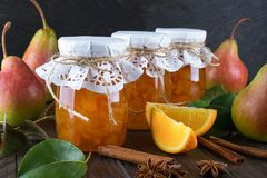 Pear and orange jam in glass jars with ripe pears, cinnamon sticks, anise stars and green leaves