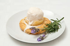 Pear Pastry. Half a tinned pear on a bed of puff pastry and topped with a scoop of vanilla ice cream and garnished with lavender and rosemary Royalty Free Stock Photos