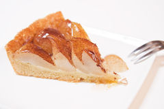 Pear pie. Succulent, juicy, freshly baked pie made with pear and sugar glaze and cinnamon. Taken on a clean white plate and background with a three pronged fork Royalty Free Stock Image